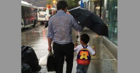 father holding umbrella