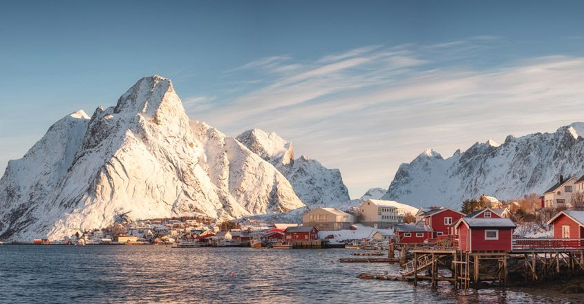 Scandinavian village with snow mountain at coastline in morning