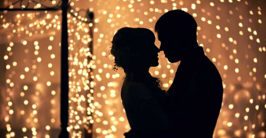 hugs-lovers-silhouette-against-background-garlands