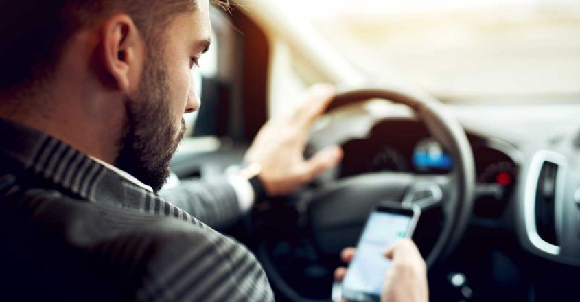 man-looking-mobile-phone-while-driving